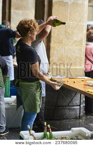 San Sebastian, Spain - September 2, 2017. Waitress Pouring Cider From A Height, The Most Tipycal Alc