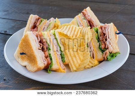 Sliced Triple Decker Turkey Club Deli Sandwich On A Plate With Potato Chips