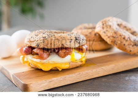 Bacon, Egg And Cheese Breakfast Sandwich With An Everything Bagel On Cutting Board