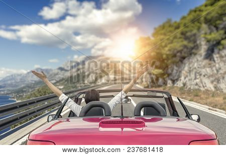 Young Woman In A Car With A Convertible On The Road To The Sea Against A Backdrop Of Beautiful Mount