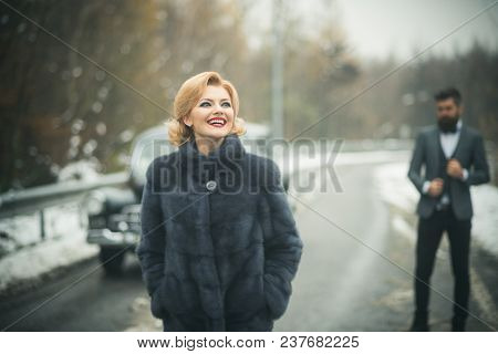 Retro Woman In Coat On Road. Couple In Love On Romantic Date. Bearded Man And Sexy Woman In Fur Coat