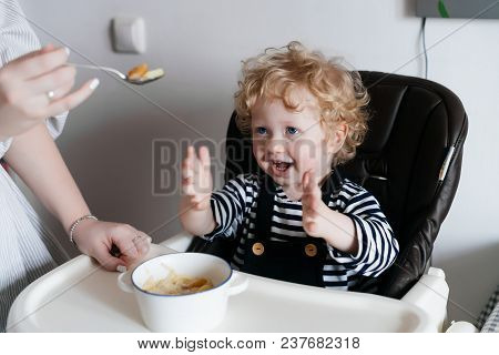 Laughing Little Baby Boy Sitting On A Highchair In The Kitchen, Eating A Useful Cereal