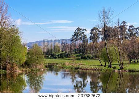 Lake or pond formed by the Pelhe river in Parque da Devesa Urban Park in Vila Nova de Famalicao, Portugal. Built near the city center