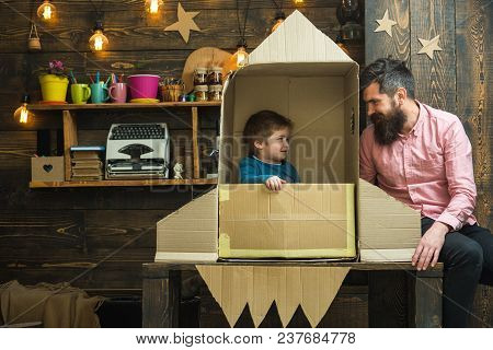 Kid Happy Sit In Cardboard Hand Made Rocket. Boy Play With Dad, Father, Little Cosmonaut Sit In Rock