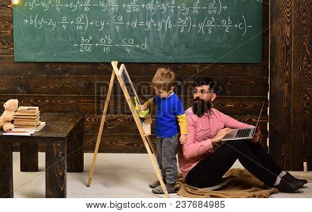 Teacher Looking At Kid Wiping Chalkboard. Side View Boy And Man Sitting On Floor With Laptop. Inform