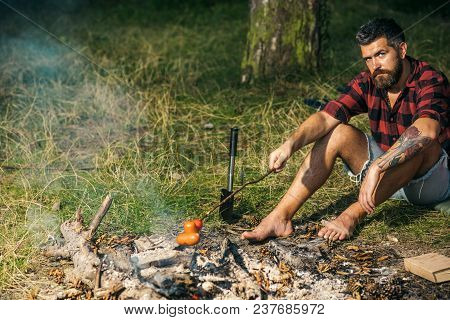 Lone Wanderer Camping In Woods. Serious Bearded Man Frying Sausages Over Fire. Barefoot Hipster Sitt