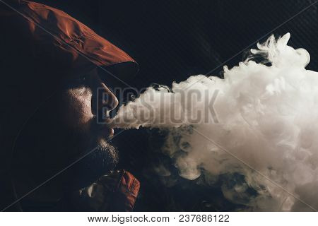 Man Vape E-cigarette With E-liquid, Close-up, Breathes Out Large Cloud Of Steam Or Vapor On Dark Bac