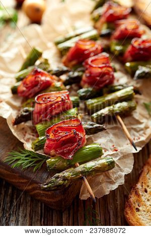 Grilled Skewers With Green Asparagus And Bacon On A Wooden Table, Top View. Grilled Food, Bbq.