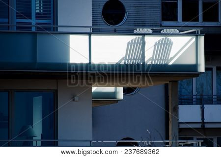 Two Sun Chairs Cast Shadows On A Balcony At A Modern Residential Building, Selected Soft Focus