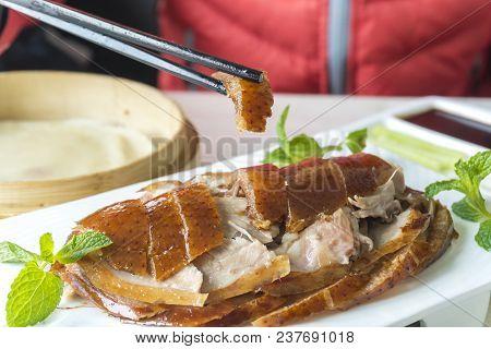 Enjoying Roasted Peking Duck In A Restaurant In Beijing