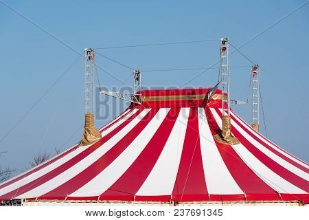 Roof Of A Circus Tent With Red And White Stripes And Four Masts Against A Blue Sky