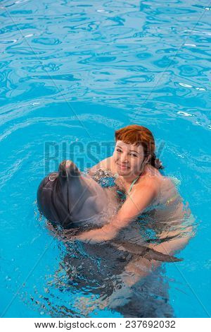 Young Happy Girl Hugs With Dolphin