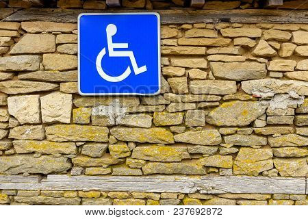Traffic Sign Indicating Parking For Persons With Disabilities Hanging On Rough Stone Wall, Disabled