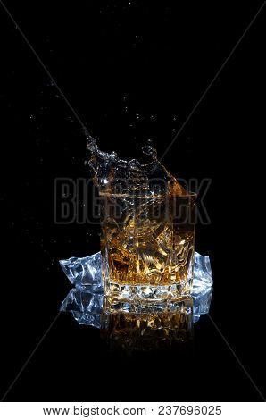 Whiskey With Splash Isolated On Black Background. Scotch With Ice In A Glass.