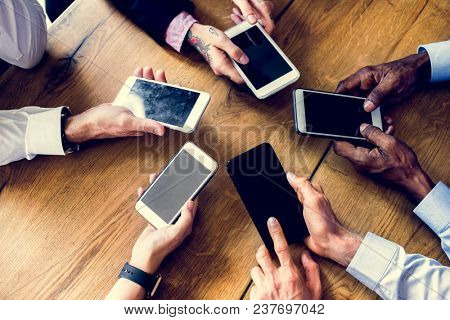 People hands using smartphone gadget in a meeting