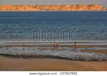 Happy Family Enjoying Sunset At The Beach.