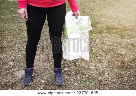 Woman With Map In Her Hands Is Standing On Ground. Girl In Hike In Wild In Mountains. Guide To Trail