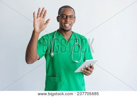 Smiling Young Doctor With Touchpad Waving Hand. Portrait Of African American General Practitioner We