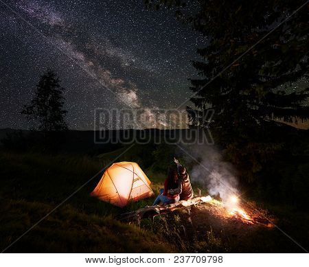 Man Pointing To The Incredible Beautiful Starry Sky And Milky Way. Couple Sitting Near The Glowing T