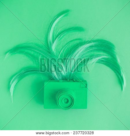 Retro Camera And Female Hair Flat Lay In Neon Green Color. Minimal Fashion Creative Concept.