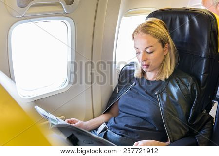Woman Reading Magazine On Airplane During Flight. Female Traveler Reading Seated In Passanger Cabin.