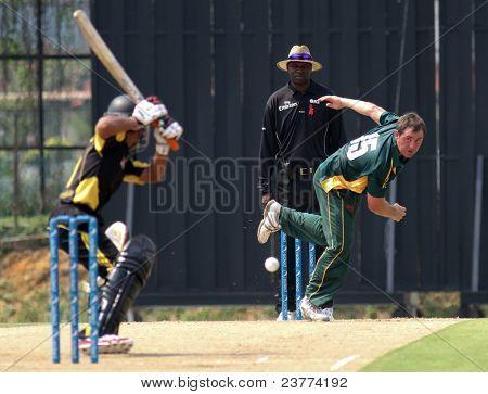 PUCHONG, MALAYSIA - SEPT 24: GM Smit, Guernsey bowls Rakesh Madhavan (5), Malaysia at the Pepsi ICC World Cricket League Div 6 finals at the Kinrara Oval on September 24, 2011 in Puchong, Malaysia.