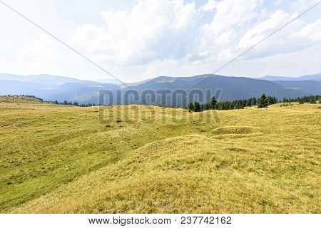 Daylight View To Green Grass Field With Mountains And Haze
