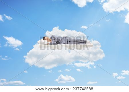 Teenage boy sleeping on a mattress up in the sky