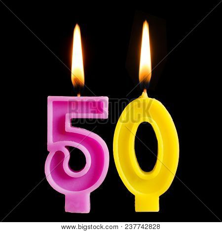 Burning Birthday Candle In The Form Of 50 Fifty Figures For Cake Isolated On Black Background. The C