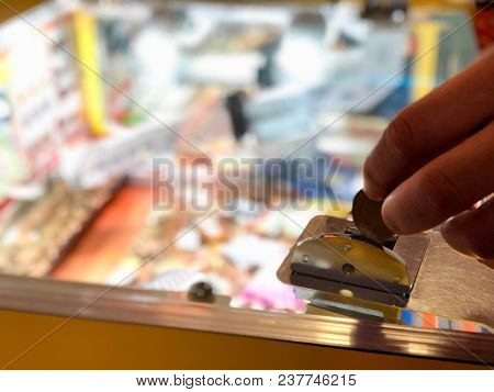 Coins being inserted by hand into a slot machine at an amusement arcade
