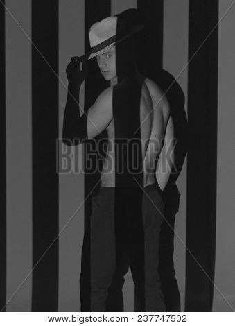 Guy In A Hat And With A Bare Torso Stands Between Black And White Stripes, Black And White Photo. La