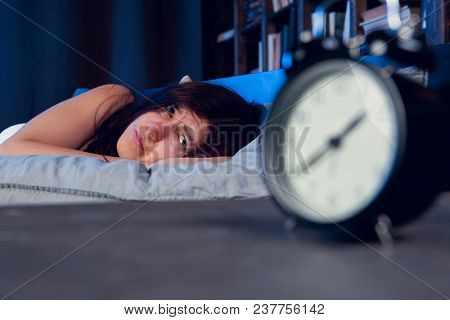 Picture of brunette with insomnia lying on bed next to alarm clock at night