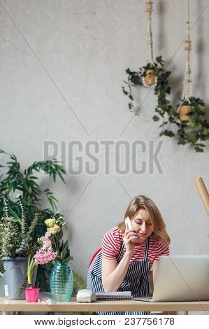Photo of florist woman talking on phone in flower shop