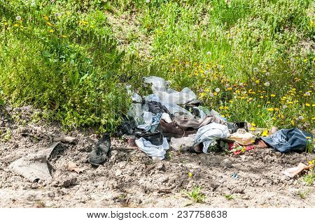 Pile Of Old Clothes And Shoes Dumped On The Grass As Junk