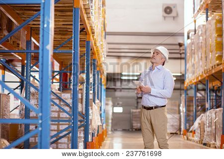 Professional Check. Nice Serious Man Looking Up While Checking The Warehouse For Safety