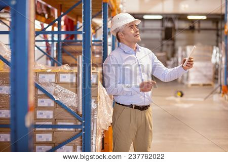 Professional Manager. Smart Skilled Man Holding A Tablet While Working As A Manager In The Warehouse