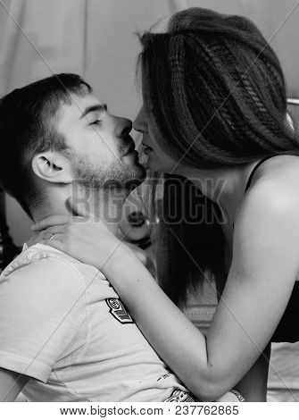 Young Beautiful Loving Couple Is Embracing On A Bed. Ntimate Image Of Sensual Couple Foreplay, Kissi