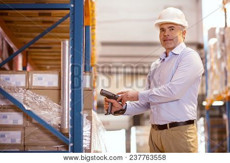 Inventory Examination. Joyful Nice Man Scanning The Boxes While Preparing Them For The Delivery