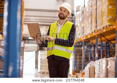 Inventory Check. Positive Delighted Man Holding His Laptop While Looking At The Boxes