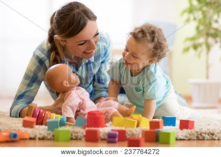 Happy Mom With Lbaby Son Playing Doll On Floor