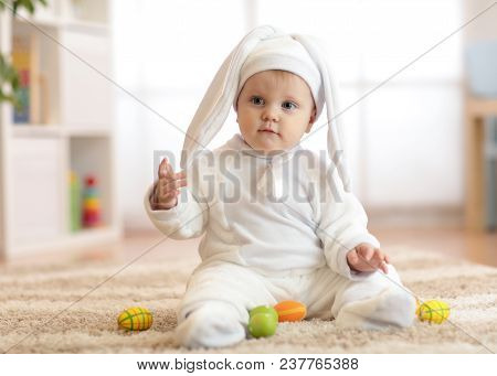 Funny Cute Baby Child In Rabbit Costume Sittng On Froor In Nursery