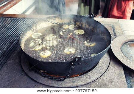 Photo Closeup Of Tea Preparation With Spices In The Old Cauldron On The Russian Stove