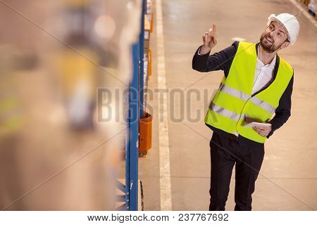 Optimization Of Space. Positive Logistics Manager Smiling While Pointing At The Box On The Storage S
