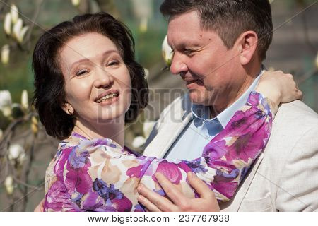 Adult Couple Walks In The Blossoming Magnolia Garden. Elegant Age Pair In The Garden Of Magnolias. W