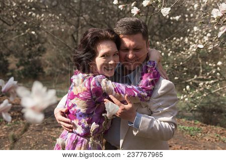 Wedding Walk. Adult Couple Walks In The Blossoming Magnolia Garden. Elegant Age Pair In The Garden O