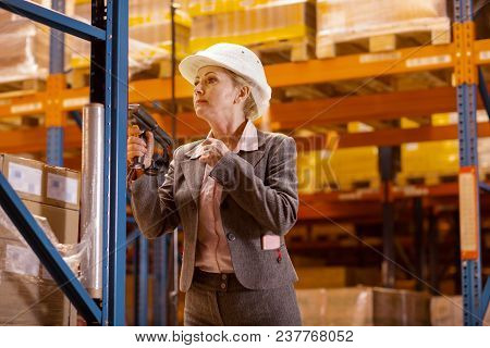 Safety Rules. Serious Pleasant Woman Wearing A Helmet While Adhering To The Safety Rules In The Ware