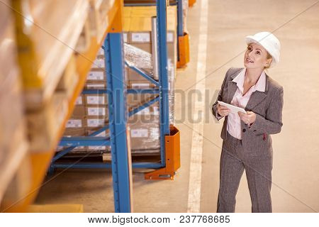 Delivery Manager. Nice Positive Woman Looking At The Storage While Working As A Delivery Manager In