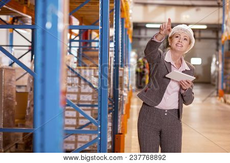 Logistics Manager. Joyful Nice Woman Smiling While Pointing The Direction For The Package