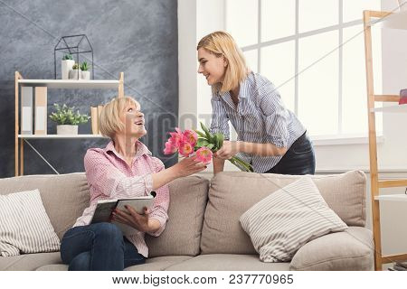 Daughter Giving Flowers To Adult Mother