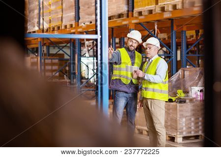 Logistics Questions. Nice Positive Man Pointing At The Storage Shelves While Talking To The Logistic